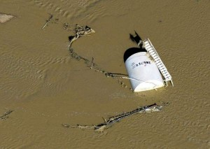 A crude oil storage tank lies on its side in floodwater after the recent floods in Colorado. John Wark/Associated Press